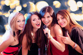 Four beautiful girls singing karaoke — Stok fotoğraf