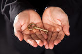 Brass key in cupped male hands — Stock Photo