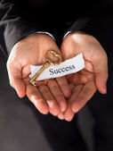 Businessman holding a golden key — Stock Photo