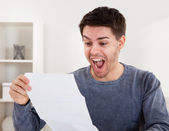 Exultant young man cheering good news — Stock Photo
