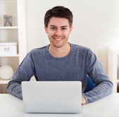 Smiling young man using a laptop — Stock Photo