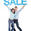 Happy young couple holding sale sign — Stock Photo