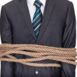 Businessman tied up in rope - Stock Photo