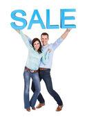 Szczęśliwa młoda para gospodarstwa sprzedaż znak — Zdjęcie stockowe