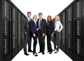 Businessteam som står på framsidan av serverrack — Stockfoto