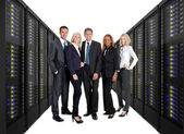 Businessteam standing on front of server racks — Stockfoto