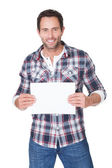 Happy middle age man presenting empty paper — Stock Photo
