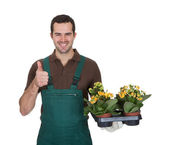 Happy young gardener holding flowers — Stock Photo