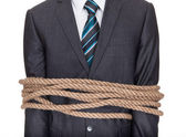 Businessman tied up in rope — Stock Photo