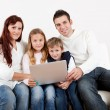 Happy family using laptop at home — Stock Photo #19638195