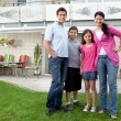 Young family standing in front of their house - Stock Photo