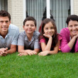 Portrait of happy young family lying on grass — Stock Photo