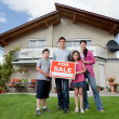 Family selling their home holding for sale sign — Stock Photo