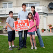 Young family holding a foreclosure sign — Stock Photo #19638259