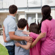 Family standing in front of their house — Stock Photo #19638269