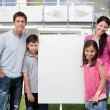 Small family standing outside with a empty sign — Stock Photo