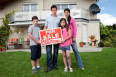 Young family holding a foreclosure sign — Stock Photo