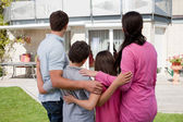 Family standing in front of their house — Stock Photo