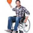 Man in wheelchair with basketball - Stock Photo