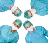 Four surgeon looking down at patient — Stock Photo