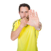 Soccer judge whistling and showing stop sign — Stock Photo