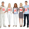 Casual group of with a brand sign board — Stock Photo