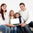 Happy young family presenting laptop — Stock Photo