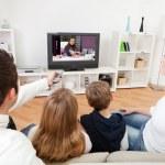 Молодая семья смотрит телевизор у себя дома — Стоковое фото