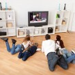 Young family watching TV at home — Stockfoto