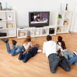 Foto Stock: Young family watching TV at home