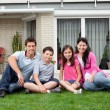 Happy family relaxing in backyard of new home - Stock Photo