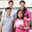 Little girl with her family holding a piggy bank — Stock Photo #19926617
