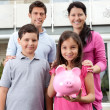 Stock Photo: Little girl with her family holding a piggy bank