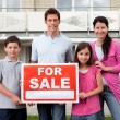 Stock Photo: Family selling their home holding for sale sign