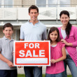 Family selling their home holding for sale sign — Stock Photo #19926655