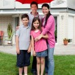 Happy family under one umbrella outside their home — Stock Photo