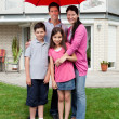 Happy family under one umbrella outside their home — ストック写真