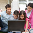 Stock Photo: Young family in backyard using laptop
