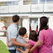 Young family standing in front of their dream home — Stock Photo