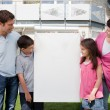 Stock Photo: Family looking at a empty board outside house