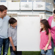 Family looking at a empty board outside house — Stock Photo