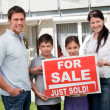Family with a sale sign outside their new home — Stock Photo