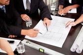 Architekti diskutovat u stolu s modrotisk — Stock fotografie