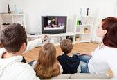 Mladá rodina doma dívat na televizi — Stock fotografie