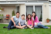 Happy family relaxing in backyard of new home — Stock Photo