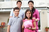 Little girl with her family holding a piggy bank — Stock Photo