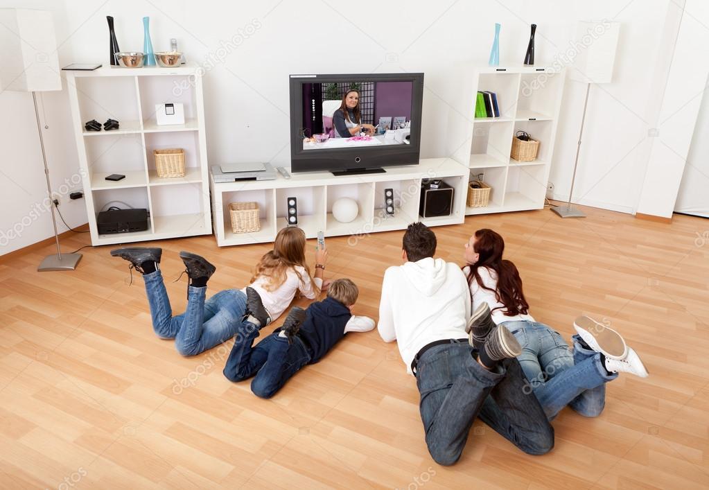 joven familia viendo la tele en casa foto stock