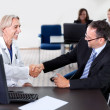 Doctor shaking hands with a patient at a desk — Stock Photo #20226539