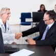 Doctor shaking hands with a patient at a desk — Stock Photo