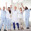 Group of happy doctors smiling and waving — Stock Photo